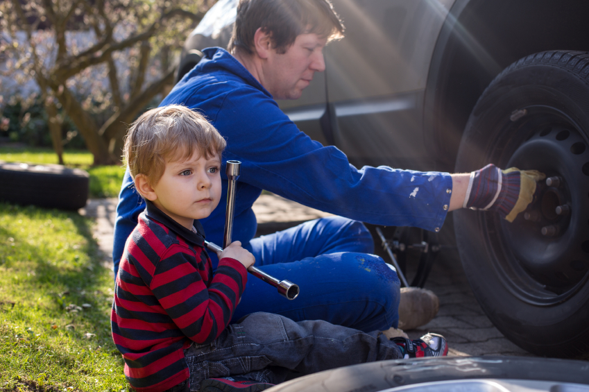 Boy of three years and his father changing wheel on car with pneumatic wrench