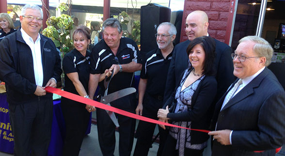 Pat and Howard Fleischmann (second and third from left) at the grand opening of a Community Tire Pros location