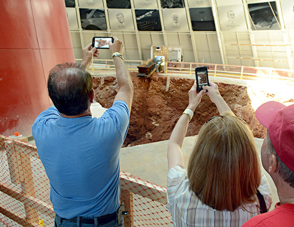 visitors take pictures of the sinkhole