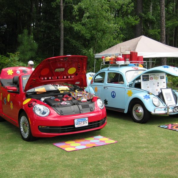 old and new Beetles decorated with flowers and peace symbol.