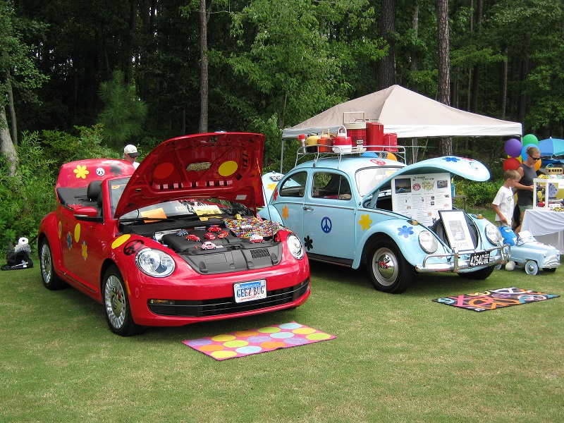 Shows old and new Beetles decorated with flowers and peace symbol.