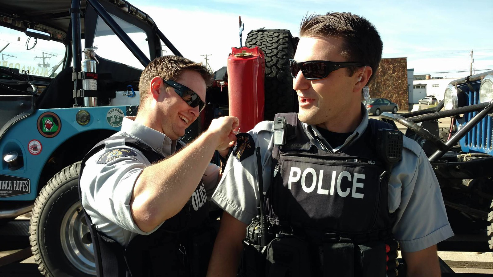 Officer removing shoulder patch to donate to Caravan